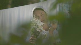 Den attraktiva höga kvinnan med den vita sjalen på hennes huvud river av tusenskönakronblad på klädstrecket utomhus washday lager videofilmer