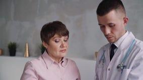 Den attraktiva höga kvinnan och den allvarliga unga caucasian doktorn talar om diagnos lager videofilmer