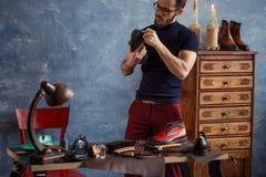 Den attraktiva hantverkaren som ger skor, tröstar och styrka royaltyfri foto