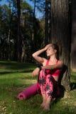 den attraktiva idrotts- kvinnan som bär den smarta klockan, tycker om sista strålar av solen för dagen efter hennes genomkörare i Royaltyfria Bilder