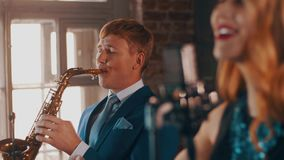 Den attraktiva jazzvokalisten som utför på etapp med saxofonisten i blått, passar live arkivfilmer