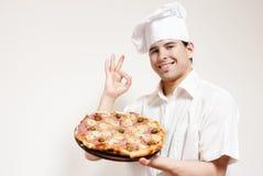 den attraktiva kocken hands lycklig pizza Royaltyfri Foto