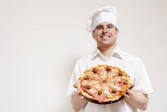 den attraktiva kocken hands lycklig pizza fotografering för bildbyråer