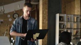 Den attraktiva koncentrerade unga affärsmannen går med en bärbar dator i hans hand och skriva Caucasian man som in arbetar lager videofilmer