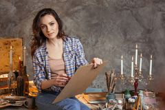 Den attraktiva konstnären som läraren i kursen av teckningen ser på på studenterna framåtriktat Hon drar olja och akryl Arkivbild