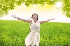 Den attraktiva kvinnan firar våren i grönt fält Fotografering för Bildbyråer