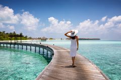 Den attraktiva kvinnan går på en träbrygga i Maldiverna royaltyfria bilder