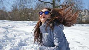Den attraktiva kvinnan i blå spegelförsedd solglasögon och rakt spela för mörkt hår kastar snöboll i parkerar utomhus i lager videofilmer