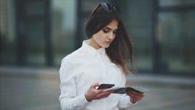 Den attraktiva kvinnan i en vit skjorta, kontrollerar biljetterna för nivån, drevet eller bussen Flickan försöker att registrera  stock video