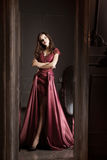 Den attraktiva kvinnan i lång bordeaux snör åt klänningen Reflekterat in avspegla royaltyfri bild