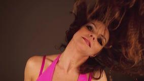 Den attraktiva kvinnan i rosa bodysuit- och strålpunktsmink dansar det rörande huvudet och att se kameran stock video