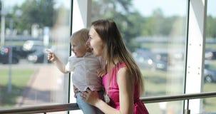 Den attraktiva kvinnan i rosa färger klär shower hennes son något i fönstret lager videofilmer