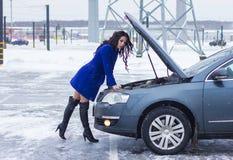 Den attraktiva kvinnan kastade hennes ben tillbaka och se under huven av hennes bil Arkivfoto