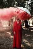 Den attraktiva kvinnan med en färgrik rökgranat bombarderar mode arkivbild