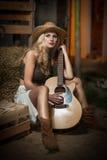 Den attraktiva kvinnan med landsblick, sköt inomhus, amerikansk landsstil Blond flicka med den sugrörcowboyhatten och gitarren ga Royaltyfri Bild