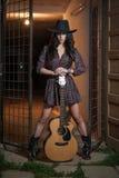 Den attraktiva kvinnan med landsblick, sköt inomhus, amerikansk landsstil Flicka med den svarta den cowboyhatten och gitarren Royaltyfri Fotografi