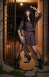 Den attraktiva kvinnan med landsblick, sköt inomhus, amerikansk landsstil Flicka med den svarta den cowboyhatten och gitarren royaltyfria bilder