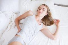 Den attraktiva kvinnan med tillbaka smärtar hemma i sovrummet, dålig säng, sjukvårdbegrepp arkivfoton