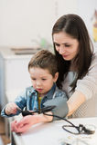 Den attraktiva kvinnan och hennes unge med ett blodtryck mäter tonometer Royaltyfri Foto