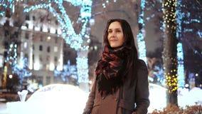 Den attraktiva kvinnan på den snöig julnatten ler se kameran av parkerar framme träd dekorerade mousserande ljus lager videofilmer