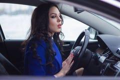 Den attraktiva kvinnan ser pensively in i vindrutan av bilen Royaltyfri Foto