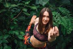 Den attraktiva kvinnan som gör mudra- och yogajämvikt, övar i djungel Fotografering för Bildbyråer