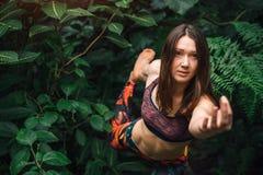 Den attraktiva kvinnan som gör mudra- och yogajämvikt, övar i djungel Arkivfoton