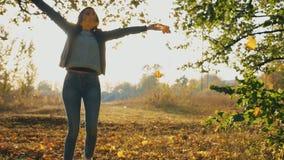 Den attraktiva kvinnan som hoppar i höstligt, parkerar och kastar gula lönnlöv Flicka som lyfter händer och tycker om ögonblick m lager videofilmer