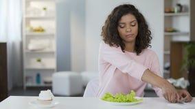 Den attraktiva kvinnan som väljer SAD sallad över kakan, bantar, viktkontroll, näring lager videofilmer