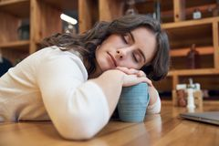 Den attraktiva långhåriga flickan faller tiredly sovande på en tabell i a Arkivfoton