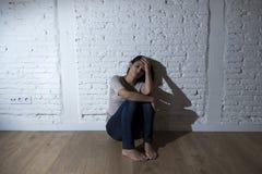 Den attraktiva latinamerikanska kvinnan som sitter det hemmastadda golvet, frustrerade lidandefördjupningen som känner sig ledsen Royaltyfri Bild