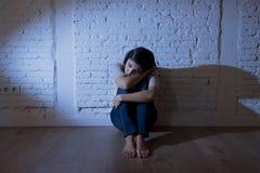 Den attraktiva latinamerikanska kvinnan som sitter det hemmastadda golvet, frustrerade lidandefördjupningen som känner sig ledsen Royaltyfri Foto