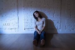 Den attraktiva latinamerikanska kvinnan som sitter det hemmastadda golvet, frustrerade suffe Arkivbilder