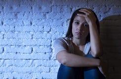 Den attraktiva latinamerikanska kvinnan som sitter det hemmastadda golvet, frustrerade suffe Arkivbild