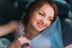 Den attraktiva le bruden i vit skyler sammanträde i bilen som ser in mot Arkivfoton
