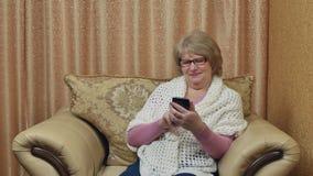 Den attraktiva le damen som använder en smartphone, meddelar på internet Lyckligt äldre kvinnasammanträde i ett bekvämt arkivfilmer
