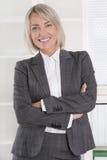 Den attraktiva le mitt åldrades affärskvinnan, i att bära för stående arkivbild