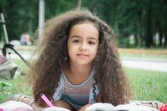 Den attraktiva lilla flickan i parkerar attraktioner på gräset royaltyfri fotografi