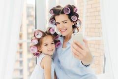 Den attraktiva lilla ungen med det positiva uttryckt, charmiga leendeställningar nära hennes moder, gör selfie med den moderna mo arkivfoto
