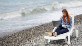 Den attraktiva ljust rödbrun kvinnan sitter på havsstranden och shoppar direktanslutet lager videofilmer
