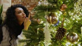 Den attraktiva lockig-hår flickan ser trädet för det nya året arkivfilmer