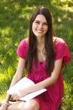 Den attraktiva lyckliga le tonåriga flickaläseboken för studenten parkerar in Arkivbilder