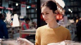 Den attraktiva lyckliga unga kvinnan väljer på lagerjulkransen dekor för hemmiljö lager videofilmer