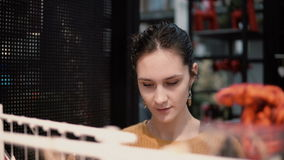 Den attraktiva lyckliga unga kvinnan väljer på lagret något gods på hyllor dekor för hemmiljö stock video