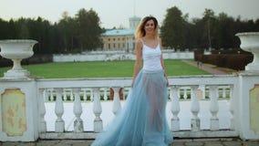 Den attraktiva magra flickan i vit och blått klär ställningar nära den vit le, dansen och som poserar för stenbalustrad under stock video