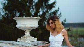 Den attraktiva magra flickan i vit- och blåttklänningställningar nära den vita stenbalustraden med blomkrukan lutar på den och se arkivfilmer