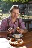 Den attraktiva mannen äter traditionell ost med kringlan i en Bayern Royaltyfri Fotografi