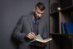 Den attraktiva mannen i en affärsdräkt läser en bok Advokaten rymmer arkivet i hans kontor Lära mannen med boken royaltyfri fotografi