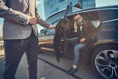 Den attraktiva mannen i solglas?gon talar vid smartphonen och sitter i bilen, medan hans assistent ?r den ?ppnande d?rren f?r hon arkivfoton