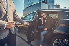 Den attraktiva mannen i solglas?gon talar vid smartphonen och sitter i bilen, medan hans assistent ?r den ?ppnande d?rren f?r hon royaltyfri bild